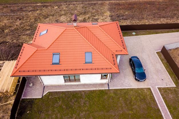 Vista aérea superior del techo de tejas metálicas de la casa con ventanas del ático y coche negro en patio pavimentado.