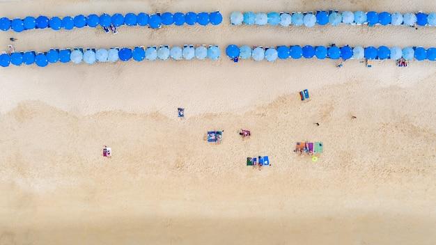 Vista aérea superior turistas que viajan durmiendo y relajarse en la playa de arena y sombrilla azul en la playa de surin, phuket, tailandia