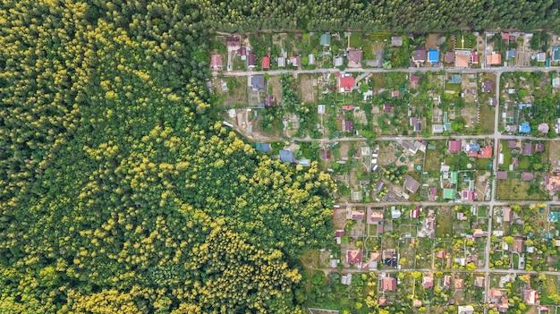 Vista aérea superior de la zona residencial de casas de verano en el bosque desde arriba, el campo inmobiliario y el pequeño pueblo de dacha en ucrania