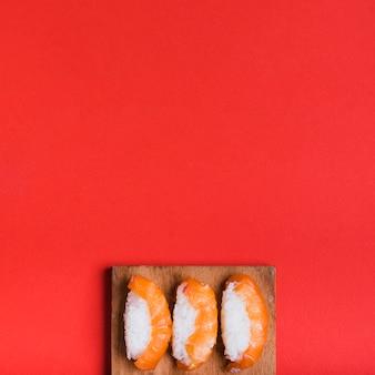 Una vista aérea de sushi clásico con salmón en tabla de cortar contra el fondo rojo