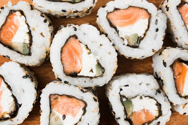 Una vista aérea de sushi con queso; sésamo; salmón y aguacate