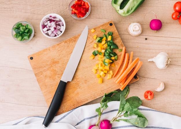 Una vista aérea de la tabla de cortar con cuchillo y verduras en el escritorio de madera