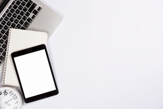 Una vista aérea de la tableta digital; bloc de notas en la computadora portátil con reloj despertador aislado sobre fondo blanco
