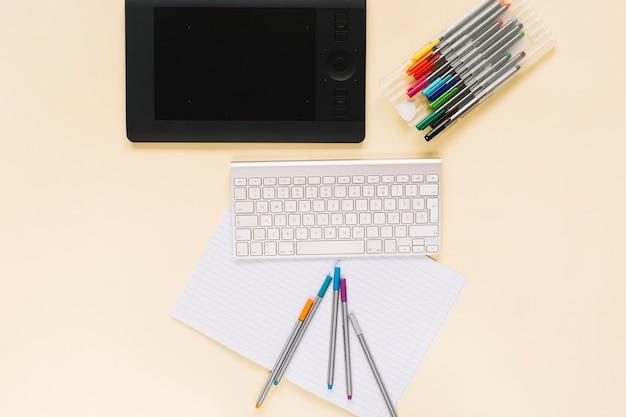 Vista aérea de la tableta digital gráfica con teclado y rotuladores en el cuaderno sobre el fondo beige