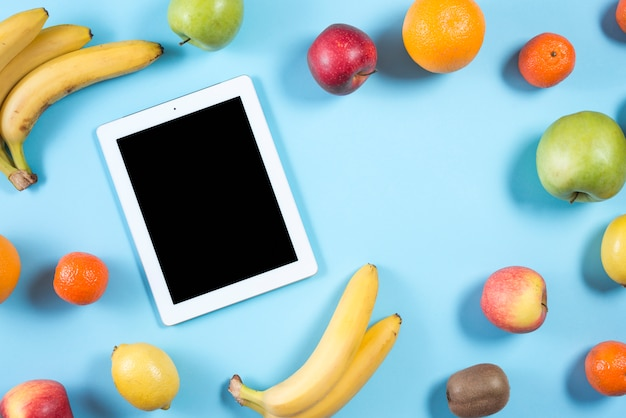 Vista aérea de una tableta digital con pantalla negra rodeada de frutas coloridas sobre fondo azul