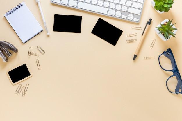 Una vista aérea de las tarjetas; bloc de notas espiral bolígrafo; anteojos y planta de cactus con teclado.