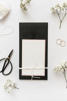 Una vista aérea de tarjetas de felicitación con tijera; anillos de boda; cadena y flor sobre fondo blanco