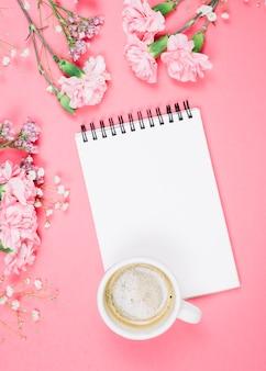 Una vista aérea de la taza de café en la libreta en blanco con claveles; gypsophila; flores de limonium sobre fondo rosa