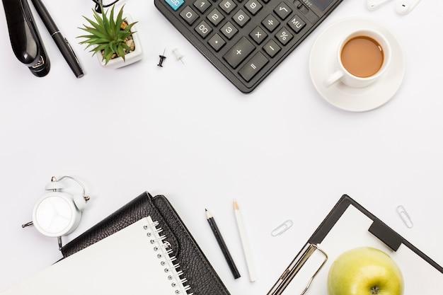 Una vista aérea de la taza de café y manzana con papelería en el escritorio