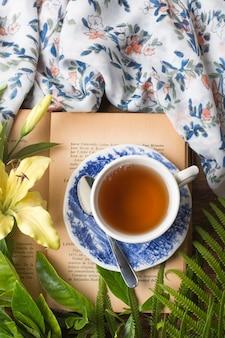 Una vista aérea de la taza de té de hierbas en el libro con hojas verdes; mantel y flor de lirio amarillo