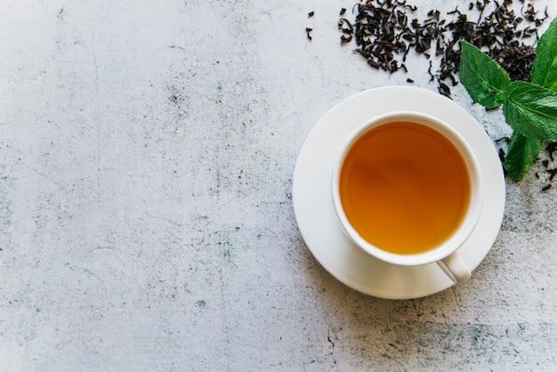 Una vista aérea de la taza de té de hierbas de menta sobre fondo de hormigón