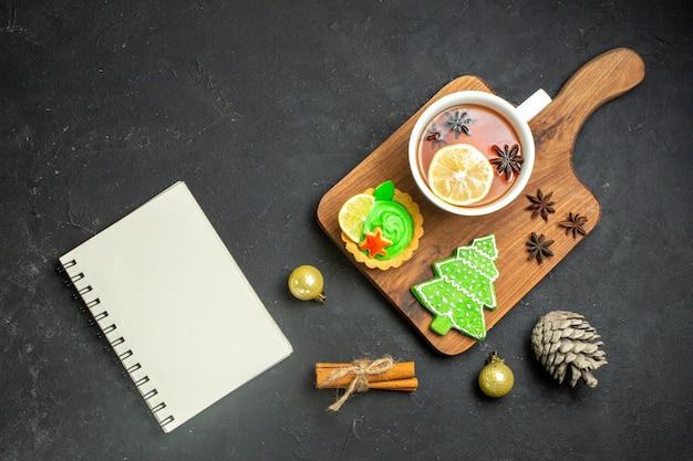 Vista aérea de una taza de té negro, accesorios navideños, cono de coníferas y cuaderno de limas canela