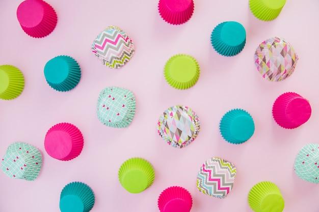 Una vista aérea de tazas de papel de cupcake colorido sobre fondo rosa