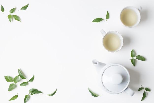 Una vista aérea de tazas de té de hierbas con hojas y tetera sobre fondo blanco