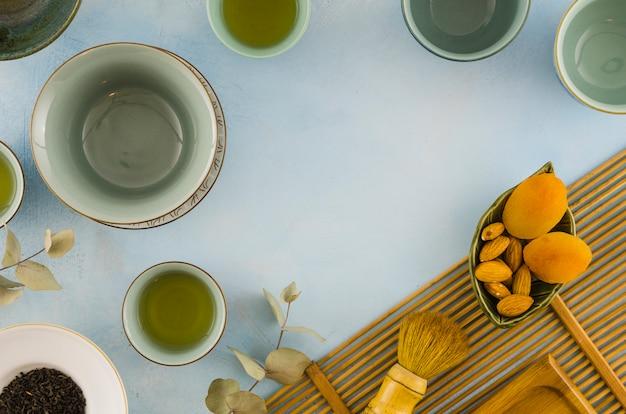 Una vista aérea de una tazas de té vacías con frutos secos y hojas sobre fondo blanco