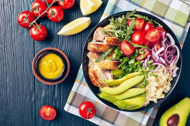 Vista aérea del tazón de pollo saludable con cuscús, verduras frescas, aguacate y rúcula en una mesa de madera negra con ingredientes, vista horizontal desde arriba, primer plano