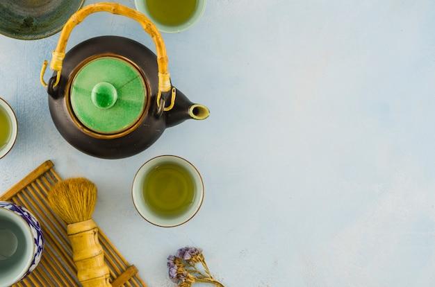 Una vista aérea de teaware chino tradicional con pincel sobre fondo blanco