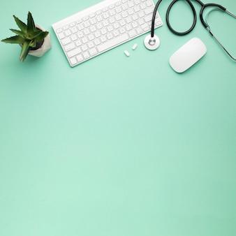 Vista aérea del teclado y mouse inalámbricos cerca del estetoscopio con píldoras y plantas suculentas