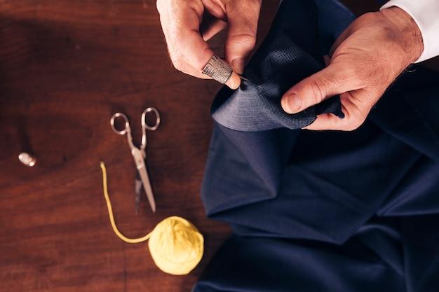 Vista aérea de la tela de costura de una mano de un hombre con aguja.