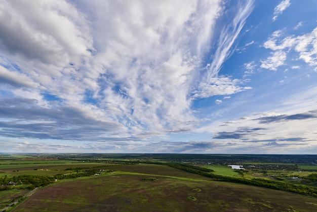 Vista aérea de tierras de cultivo bajo un cielo azul con nubes.