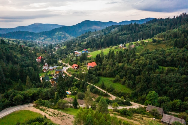 Vista aérea tomada por drone village pequeño entre montañas, bosques, arrozales