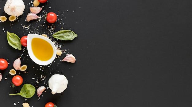 Vista aérea de tomate cherry ecológico; hojas de albahaca; ajo y tazón de aceite de oliva sobre superficie negra.