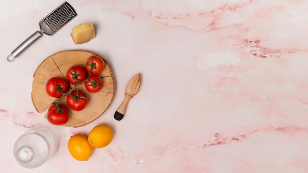 Vista aérea de tomates rojos frescos de granja y limón con cubiertos de cocina
