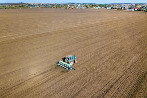 Vista aérea de un tractor arando el campo de granja agrícola negro después de la cosecha en otoño.