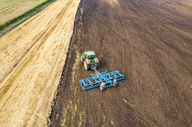 Vista aérea de un tractor arando el campo de granja agrícola negro a finales de otoño.