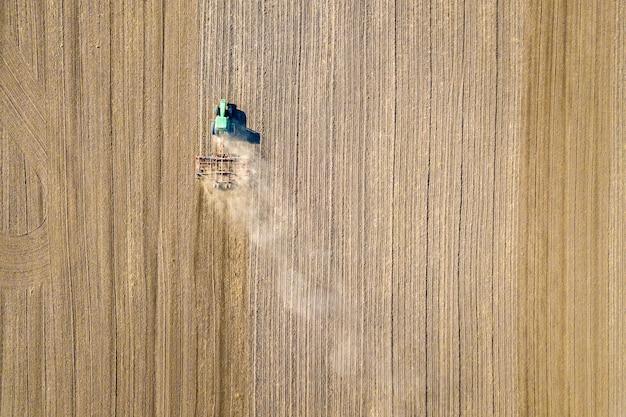 Vista aérea de un tractor arando el campo de granja agrícola negro en otoño.