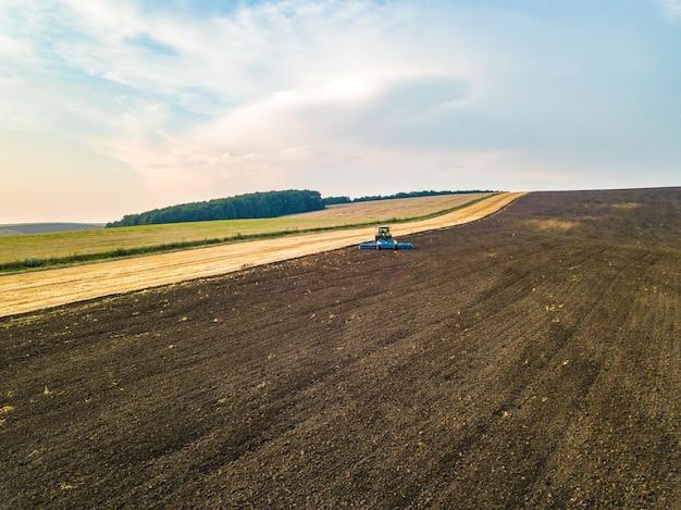 Vista aérea de un tractor arando el campo de la granja de agricultura negra después de la cosecha a finales de otoño.