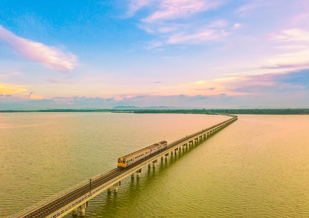 La vista aérea de los trenes pasa a través del lago de la presa en el cielo de la puesta del sol