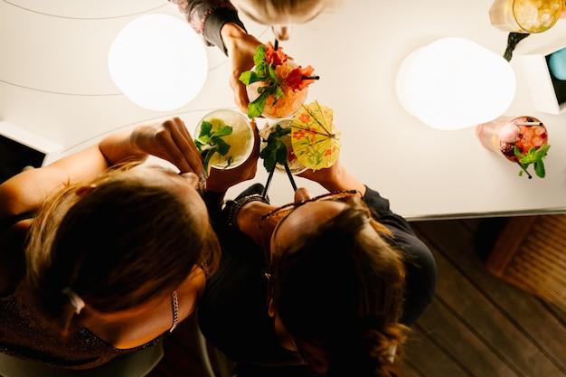Vista aérea de tres mujeres bebiendo cócteles con una pajita juntos en la noche