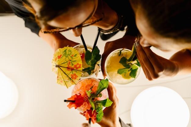 Vista aérea de tres mujeres bebiendo cócteles con una pajita juntos