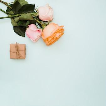 Una vista aérea de tres rosas y una caja de regalo envuelta en un fondo azul pastel