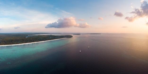 Vista aérea tropical playa isla arrecife mar caribe al atardecer.