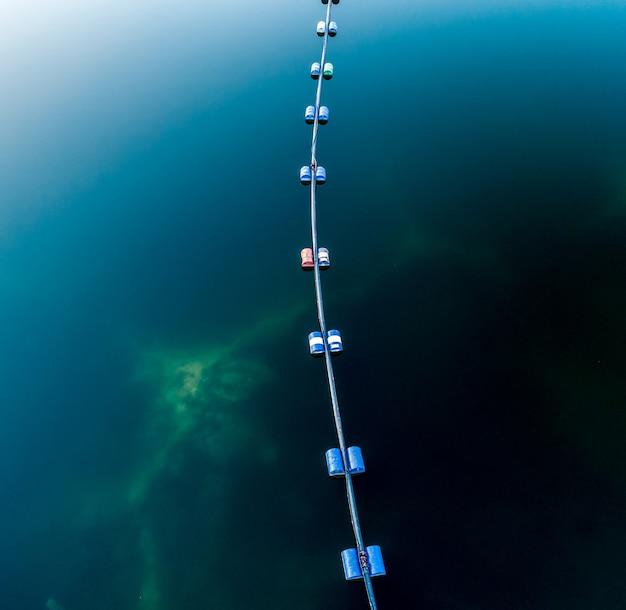Vista aérea del tubo azul con barriles en el lago