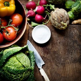 Vista aérea de varios vegetales frescos con cuchillo y madera cortada.