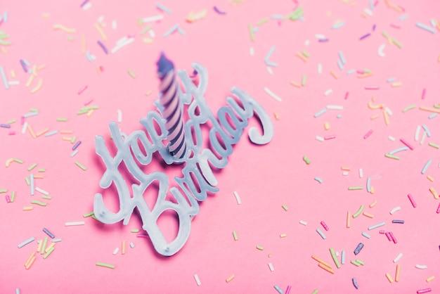 Vista aérea de la vela sobre el texto feliz cumpleaños y espolvorear sobre fondo rosa
