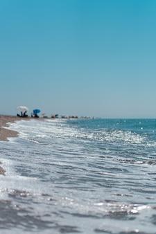 Vista aérea vertical de las olas del océano turquesa que llegan a la costa