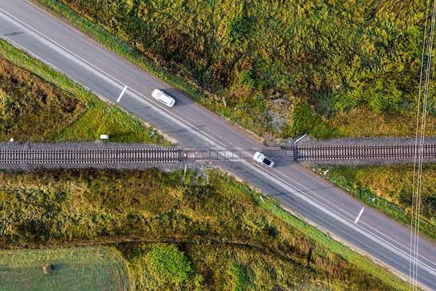 Vista aérea de las vías del tren que cruzan una carretera asfaltada con coches en zona rural