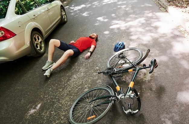 Vista aérea. víctima en el asfalto. bicicleta y accidente de coche de color plateado en la carretera en el bosque durante el día