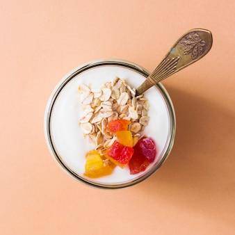 Vista aérea de yogur en el frasco de vidrio abierto con una cuchara sobre un fondo naranja