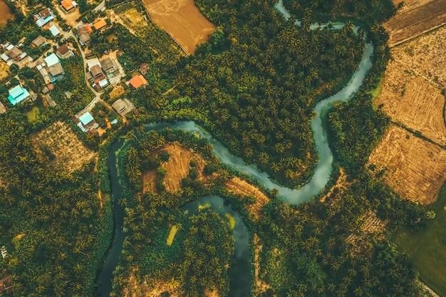 Vista aérea desde zánganos de río tortuoso y área agrícola.