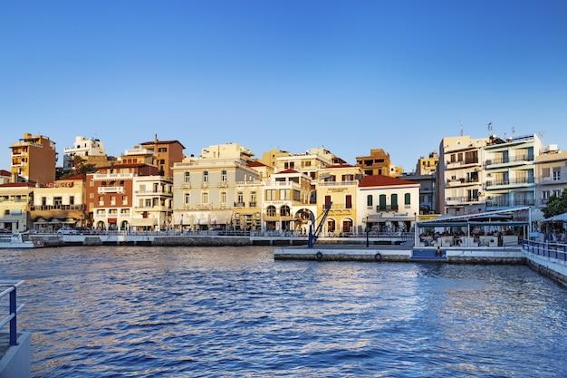 Vista de agios nikolaos al atardecer. por la noche cafés al aire libre en el paseo marítimo. grecia, isla de creta