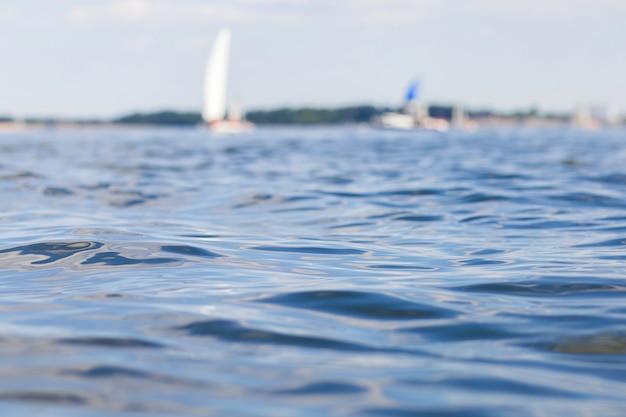 Vista del agua del río, yates borrosos y barcos con velas.