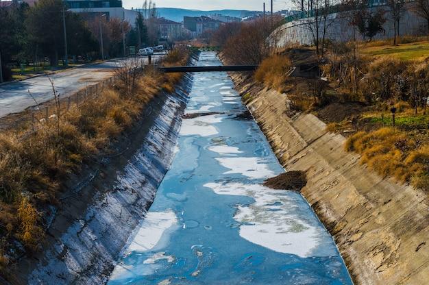 Vista de aguas residuales, contaminación y basura en un canal.