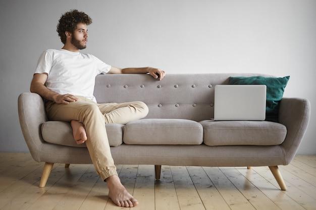 Vista aislada del joven pensativo con los pies descalzos sentado en el interior en el sofá con el portátil genérico abierto, con un pequeño descanso mientras trabaja lejos de casa. personas, trabajo, ocupación y tecnología