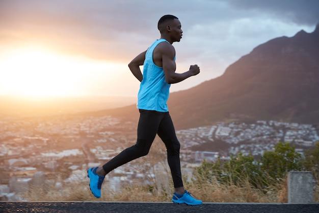 La vista al aire libre del corredor masculino joven activo cubre un largo destino en la mañana al amanecer, corre sobre la vista de las montañas, tiene bíceps, está vestido con ropa deportiva, respira profundamente, disfruta del clima de verano.