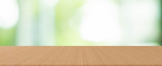Vista al jardín borrosa forma la ventana de la sala de estar con fondo de mostrador de mesa de madera